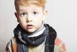 fashionable handsome little boy in scarf.stylish haircut.fashion