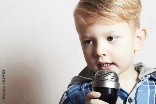 little boy singing into a microphone. child in karaoke