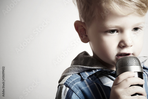 little boy singing into a microphone. child in karaoke.fashion