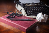 Antique red book and pen, glasses with old typewriter
