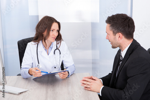 Female Doctor Looking At Businessman