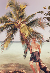 Teenager at palm tree and ocean in the background