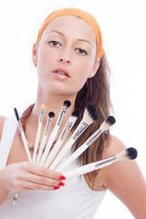 Hübsche Frau hält Kosmetikpinsel