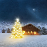 Fototapety Illuminated Christmas tree in Alpine winter landscape