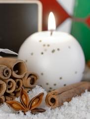 Kerze mit Sternanis und Zimtstangen