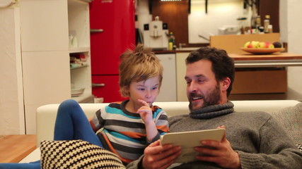 Father and Son with digital tablet at home
