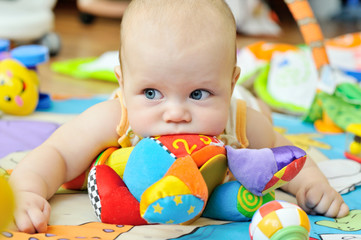 blue-eyed baby with toys