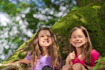 Zwei Mädchen beim spielen auf altem Baum