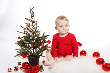 Baby boy with christmas tree and balls