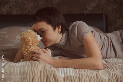 Girl lying on the bed with a teddy bear