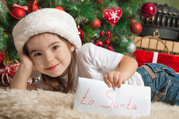 Happy little girl with letter to Santa near christmas tree