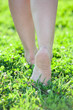 Barefoot women legs stepping on green grass