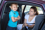 Mother trying to ask child get in safety seat against wishes