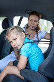 Unhappy girl sitting in child safety seat against the wishes