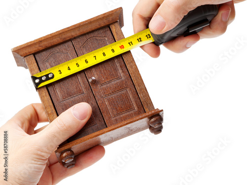 woodworker measuring wardrobe with a tape measure, carpentry con - 58708884