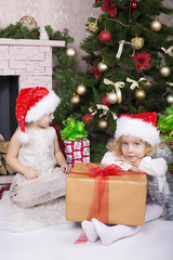 little girls in Santa's hat  with Christmas gifts