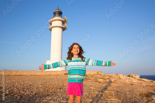 Happy open arms kid girl in Mediterranean lighthouse