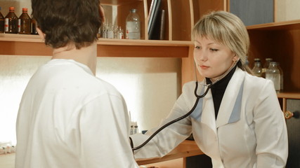 doctor woman listening through a stethoscope bronchi men