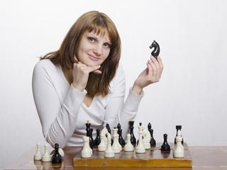 девушка с фигурой коня за шахматной доской
