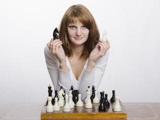 девушка держит в руках две фигуры шахматного коня