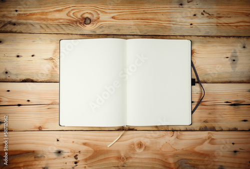 Open blank notepad with empty white pages  laying on a wooden ta