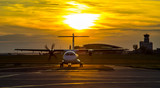 Fototapety Propeller plane taxiing around the airport at sunset