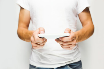 Man in white t-shirt using mobile smart phone,white wall on back