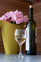 Flowers, a bottle and a glass of wine
