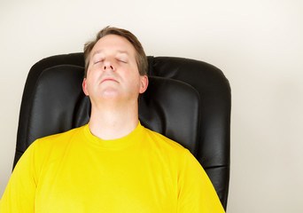 Mature Man Relaxing in Massage Chair