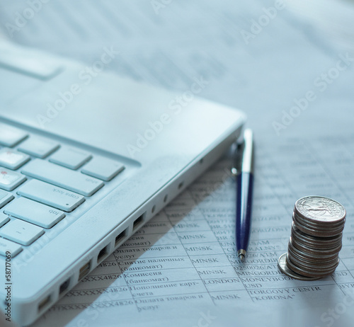 coins and pen near laptop