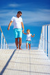 happy father and son walking on blue sky horizon