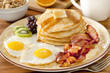 breakfast plate with pancakes, eggs, bacon and fruit.