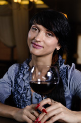 Young woman smiling while drinking red wine