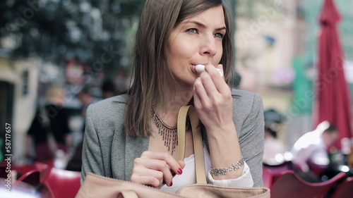 Pretty businesswoman applying pink lipstick on her lips in city