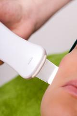 Beauty spa salon. Woman getting ultrasound skin cleaning