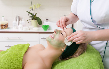 Beauty salon. Cosmetician removing facial mask from woman face.