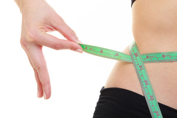 Weight loss. Green measuring tape on woman body