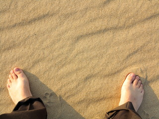 wavy yellow sand texture background and male feet