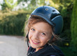 Happy little girl in helmet for horseriding