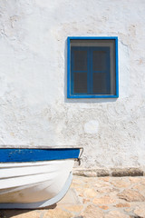 Mediterranean boat and whitewashed wall in white and blue