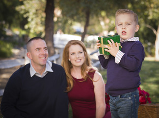 Young Boy Holding Christmas Gift in Park While Parents Look