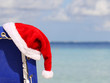 Santa's Hat on chair lounge on tropical caribbean beach.