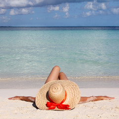 Woman in Big Sun Hat from relaxing on Tropical Beach.