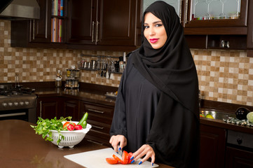 Arabian woman wearing hijab cutting veggies in the kitchen