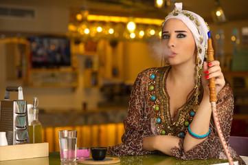 Arabian girl holding the hookah pipe in a coffee shop