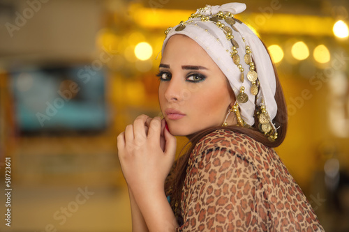 Arabian Woman posing in front of a golden background