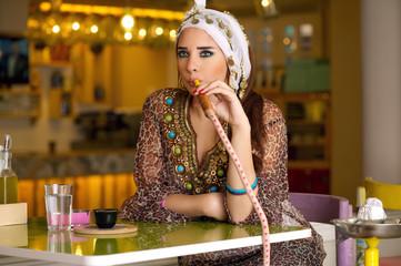 Arabian lady smoking hookah in the coffee shop