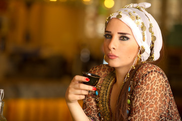 Beautiful Arabian model drinking coffee