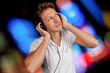 Mann mit Kopfhörern und bunten Lichtern im Hintergrund