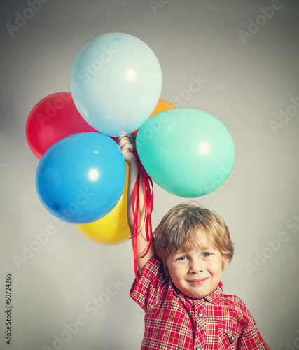 Boy holding the bunch of balloons